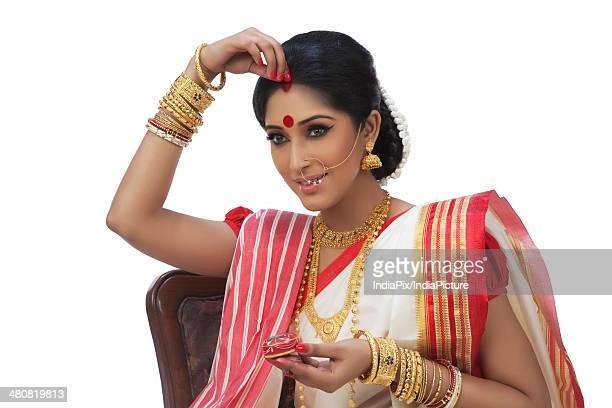 Beautiful woman putting sindoor on forehead