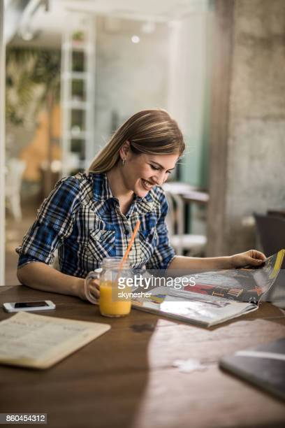 Beautiful woman reading a magazine while relaxing in a cafe.