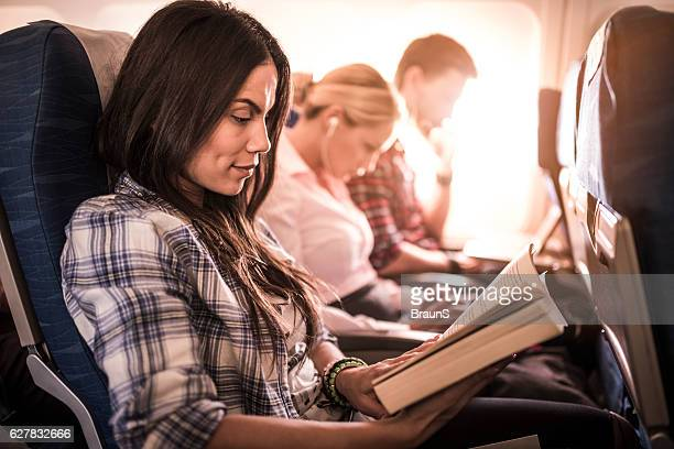 Beautiful woman reading a novel in the airplane.