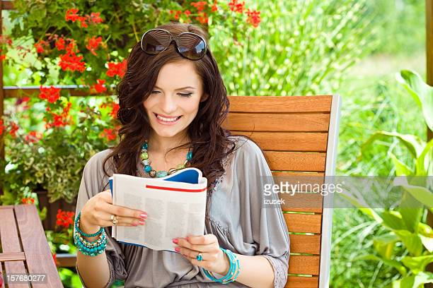 Beautiful woman reading magazine