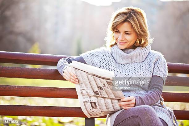 Beautiful woman reads a newspaper at the park.