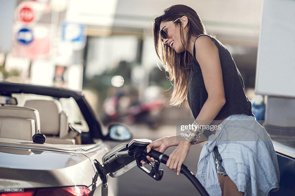 Beautiful woman refueling the gas tank at fuel pump.