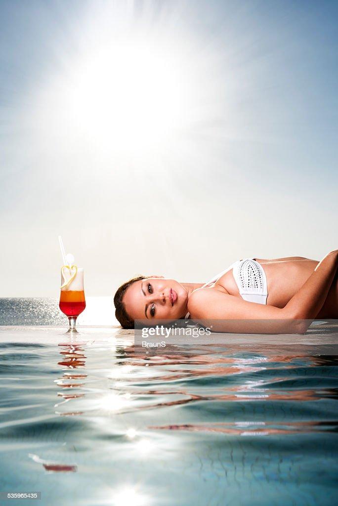 Beautiful woman relaxing at infinity pool. : Stock Photo