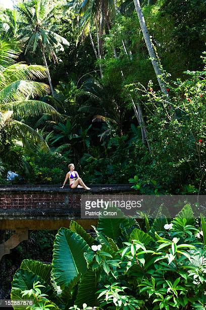 A beautiful woman relaxing on a bridge next to a hot springs surrounded by a lush jungle and flowers in Bali, Indonesia.