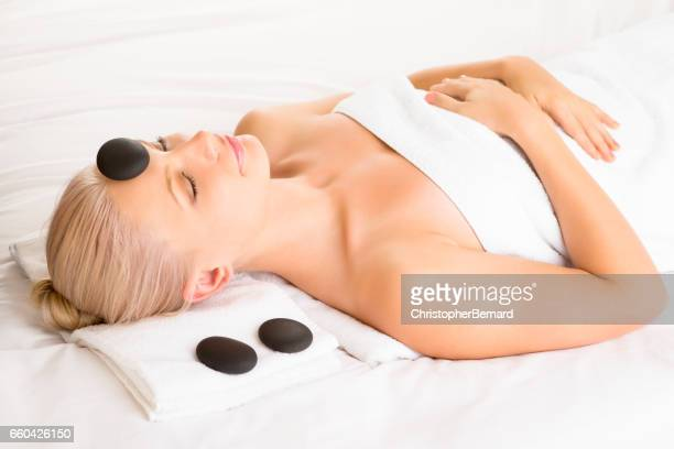 Beautiful woman relaxing while having la stones therapy