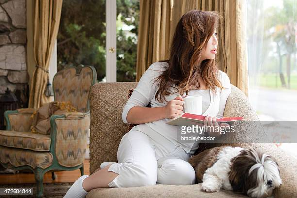 Beautiful woman relaxing with her dog and book at home