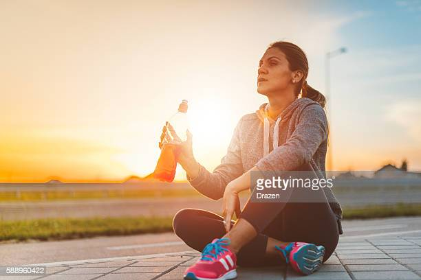 Beautiful woman resting after training and drinking energy drink