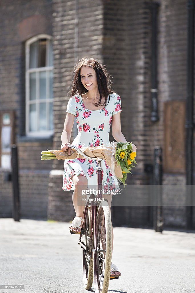 Beautiful woman riding a bicycle with sunflowers