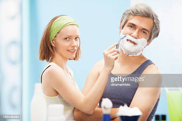 Beautiful woman shaving handsome man