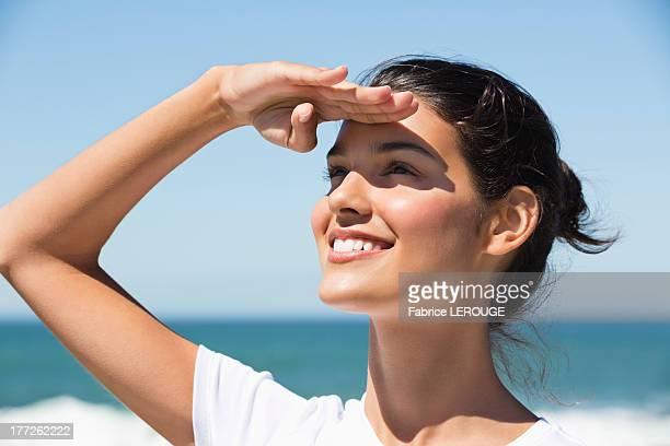 Beautiful woman shielding eyes on the beach