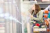 Happy woman shopping for frozen food with smart phone.