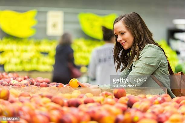 Schöne Frau Geschäfte im Markt für Obst