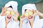 beautiful woman showing fresh lemon in spa
