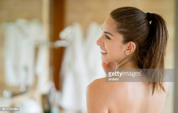 Beautiful woman showing her nude back in the bathroom