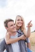 Beautiful woman showing something to man while enjoying piggyback ride at field