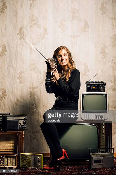 Beautiful Woman Sitting among Vintage Televisions and Radio