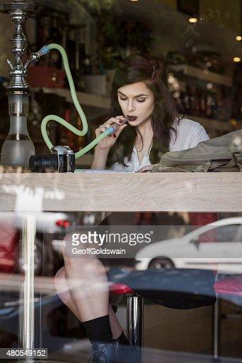 beautiful woman sitting at shop window smoking : Stock Photo