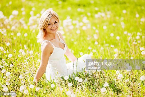 Belle femme assis dans le champ de fleurs.