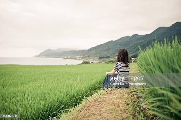 Beautiful woman sitting in the paddy fields.