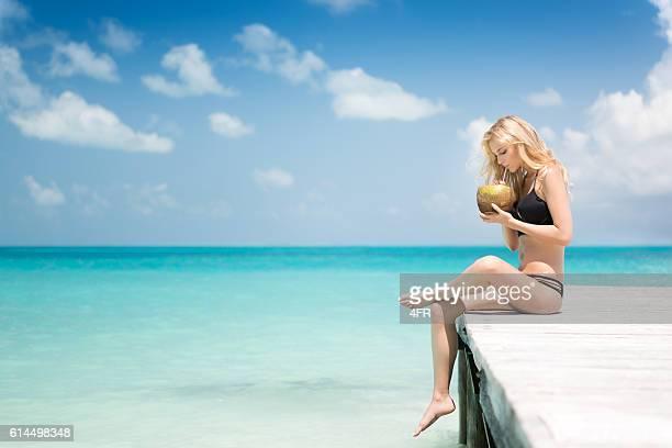 Beautiful woman sitting on a pier drinking a fresh Coconut