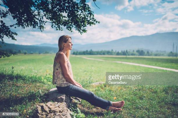 Beautiful Woman Sitting on a Rock in Countryside