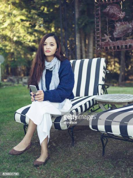 beautiful woman sitting on armchair at yard of house