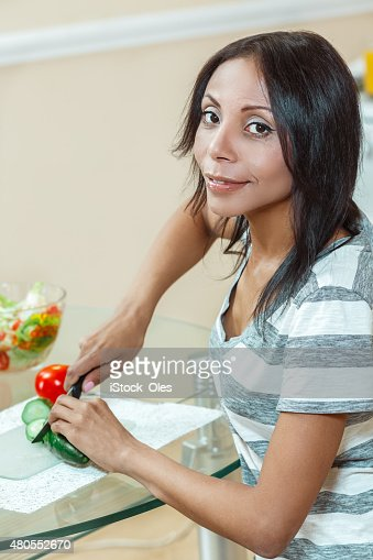 Linda mulher cortar pepino na cozinha moderna para salada : Foto de stock