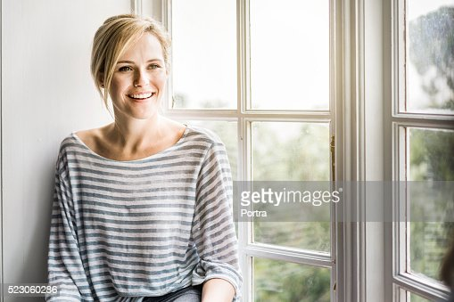 Beautiful woman smiling by window at home