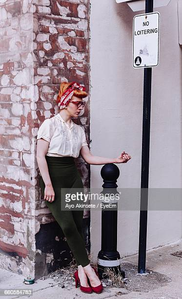 Beautiful Woman Standing On Bollard On Footpath At City