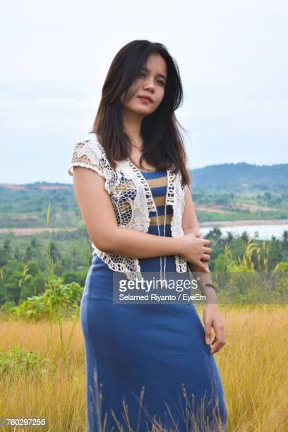Beautiful Woman Standing On Grassy Field Against Clear Sky