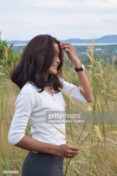 Beautiful Woman Standing On Grassy Field Against Sky
