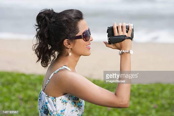 Belle femme debout sur prairie et filmer et un caméscope