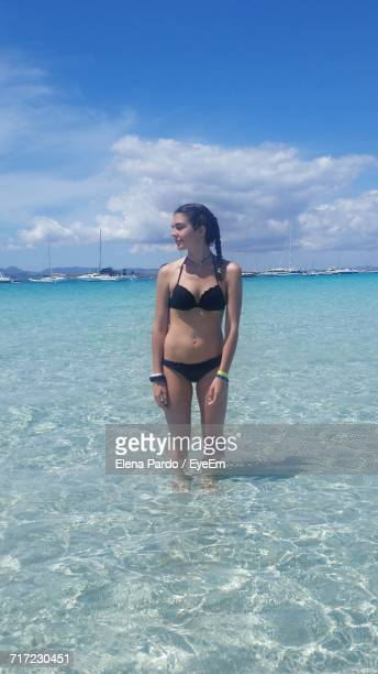 Beautiful Woman Standing On Shore Against Sky During Sunny Day