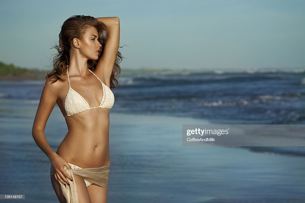 Beautiful woman standing on the beach : Stock Photo