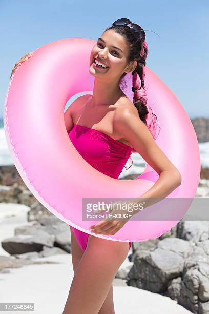 Beautiful woman standing with an inflatable ring on the beach