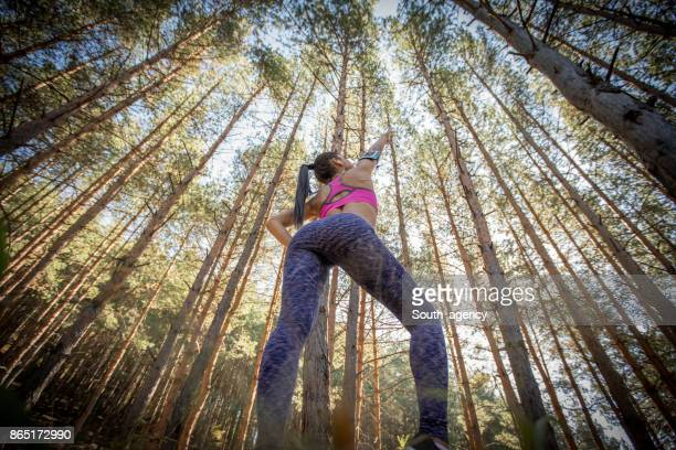 Beautiful woman stretching in forest