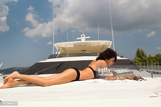 Beautiful woman sunbathing and relaxing on a luxury yacht