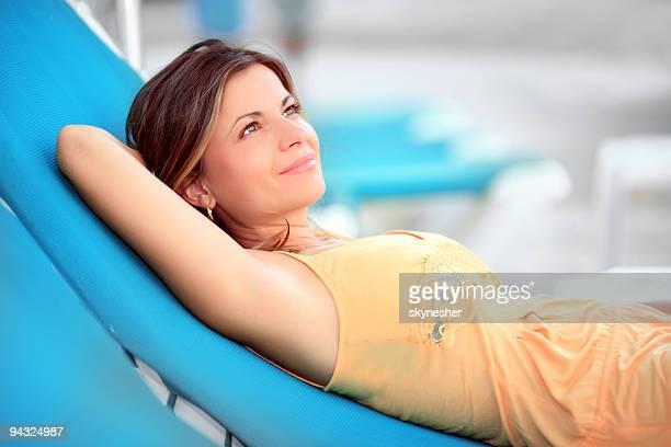 beautiful woman sunbathing by the pool