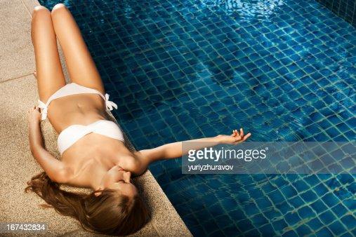 Beautiful woman sunbathing near swimming pool : Stock Photo