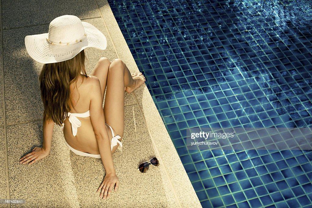 Hermosa mujer tomando el sol cerca de la piscina : Foto de stock