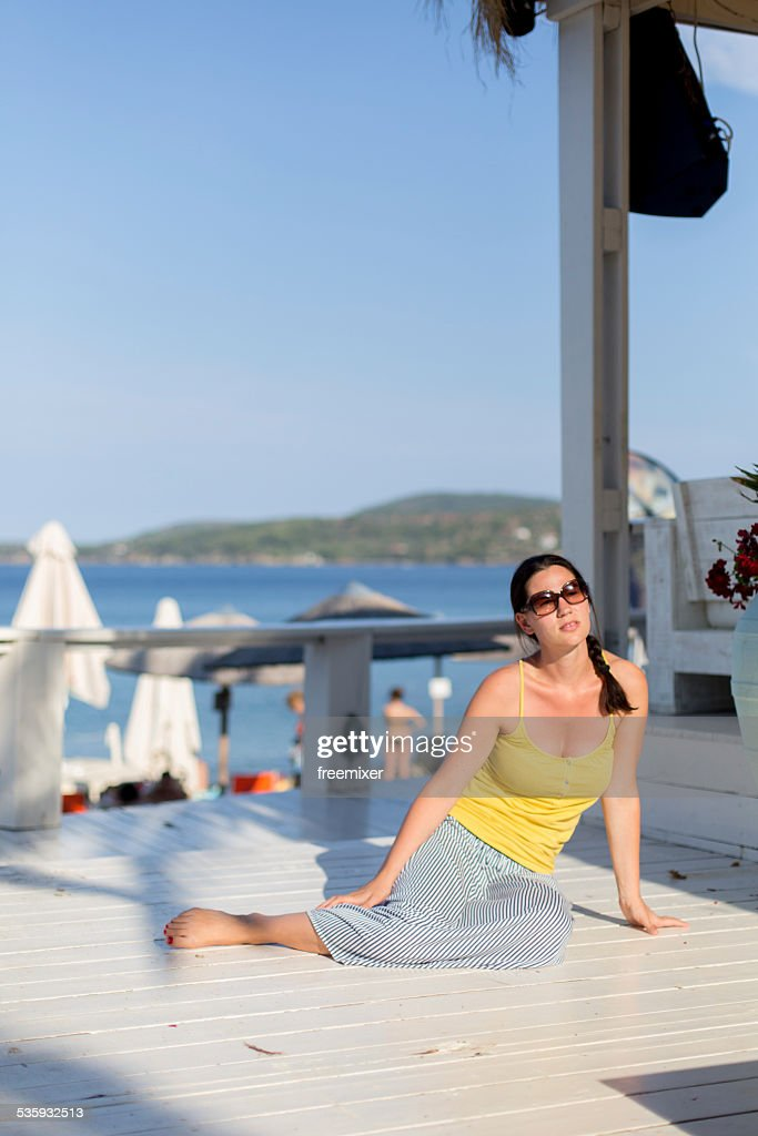 Beautiful woman sunbathing on a porch : Stock Photo