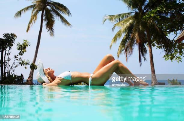 Beautiful woman sunbathing on the edge of swimming pool