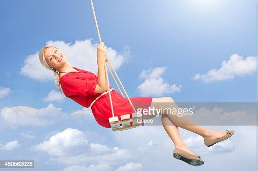 Beautiful woman swinging on a swing outdoors : Stock Photo