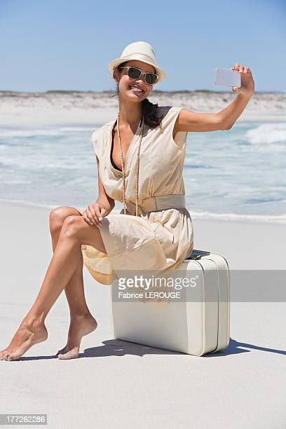 Beautiful woman taking a picture of herself with a cell phone on the beach