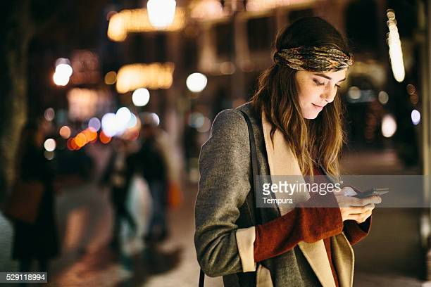 Beautiful woman texting at night in Barcelona.