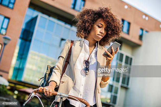 Beautiful woman texting on the phone with the bike