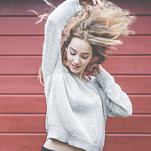 Beautiful Woman Tossing Hair Against Wooden Plank