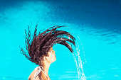 Beautiful woman tossing her wet hair in swimming pool