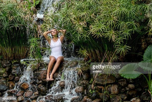 Beautiful woman under a waterfall