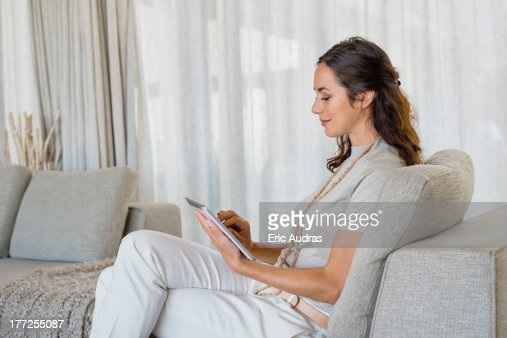 Beautiful woman using a digital tablet and smiling on a couch : Stock Photo